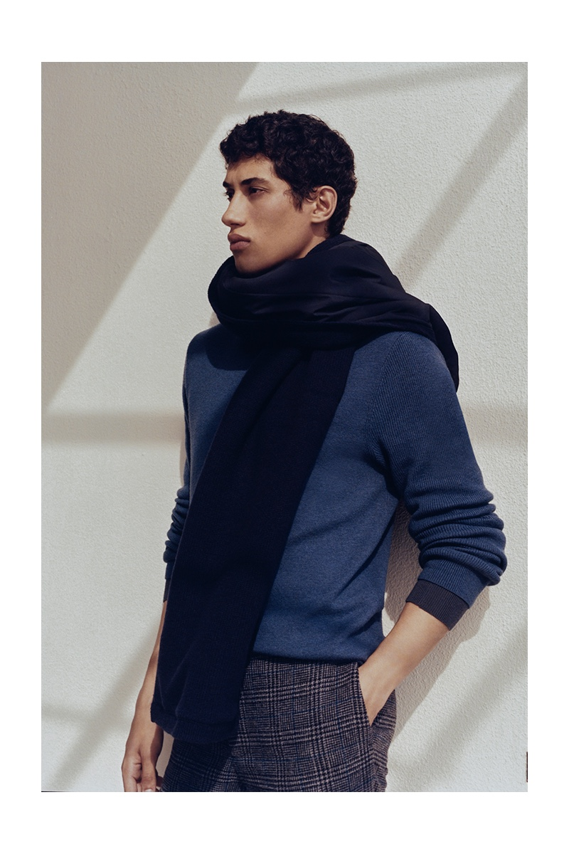 Front and center, Malik Al Jerrari dons an oversized scarf with a blue sweater  and glen plaid dress pants by Club Monaco.