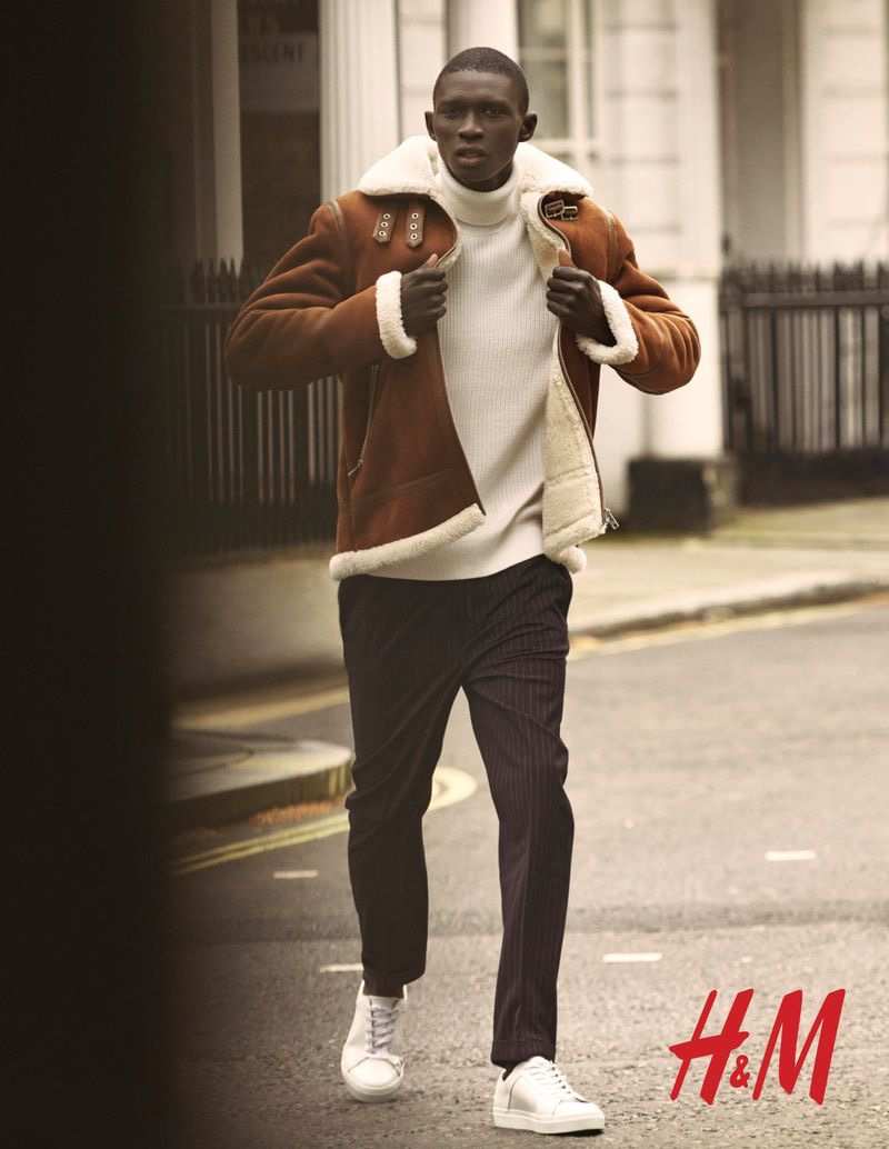 Portuguese model Fernando Cabral dons a faux suede shearling jacket with a ribbed sweater and striped trousers from H&M.