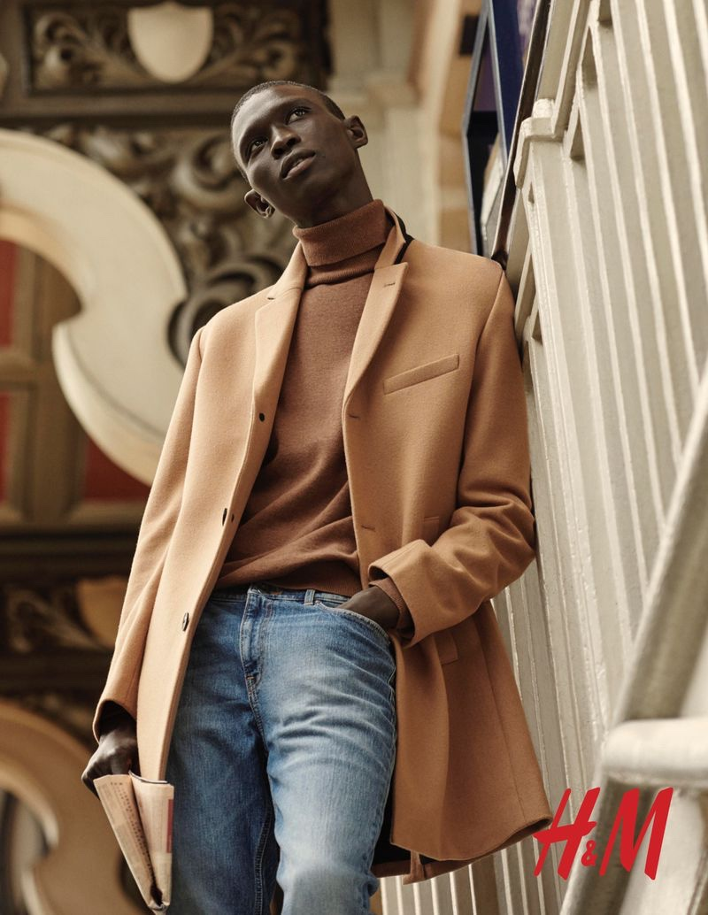 Fernando Cabral dons a camel-colored coat with a brown turtleneck sweater and light wash jeans from H&M.