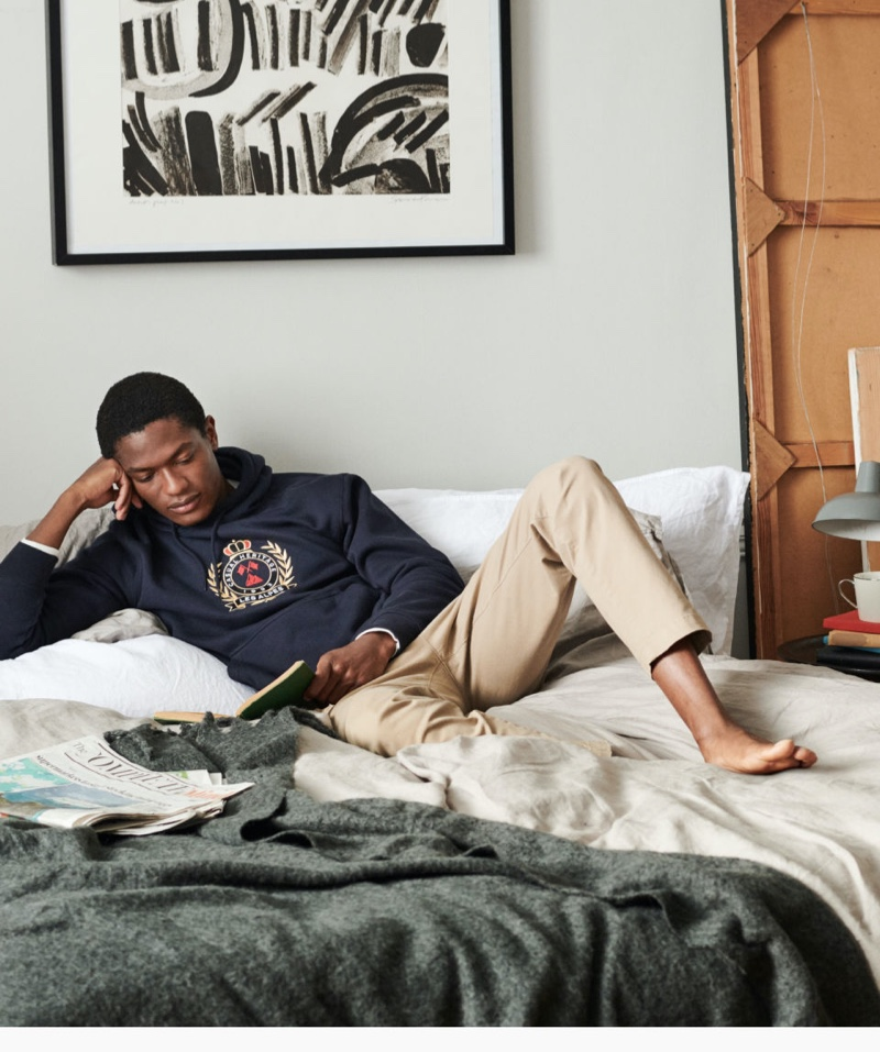 Relaxing in bed, Hamid Onifade dons a printed hooded sweatshirt from H&M.