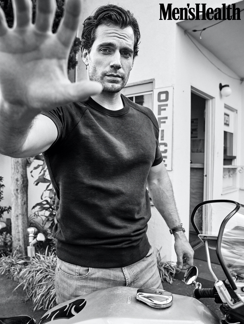 Actor Henry Cavill sports a sweatshirt by Todd Snyder + Champion with 7 For All Mankind jeans and a Timex watch.