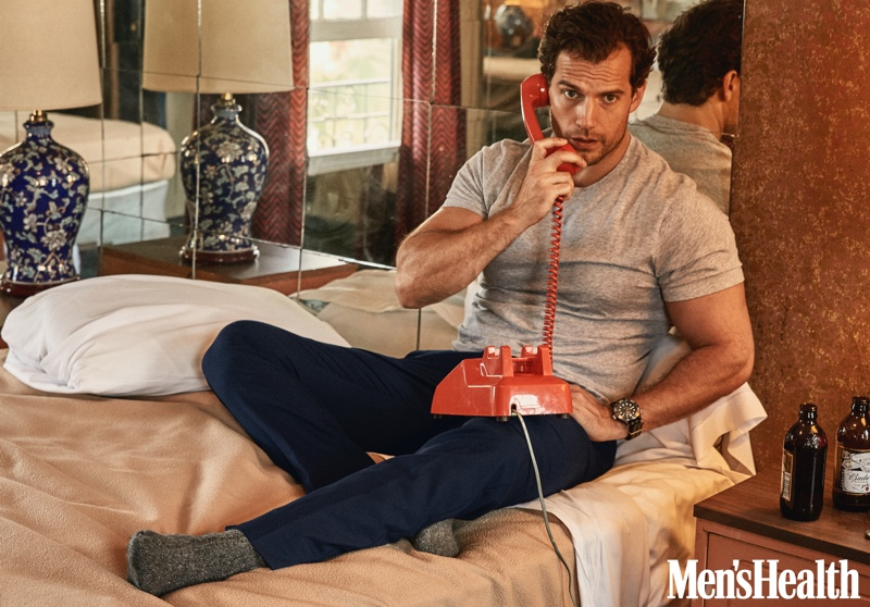 Taking a phone call, Henry Cavill dons an Armani Exchange t-shirt with Tommy Hilfiger pants, an Omega watch, and American Trench socks.