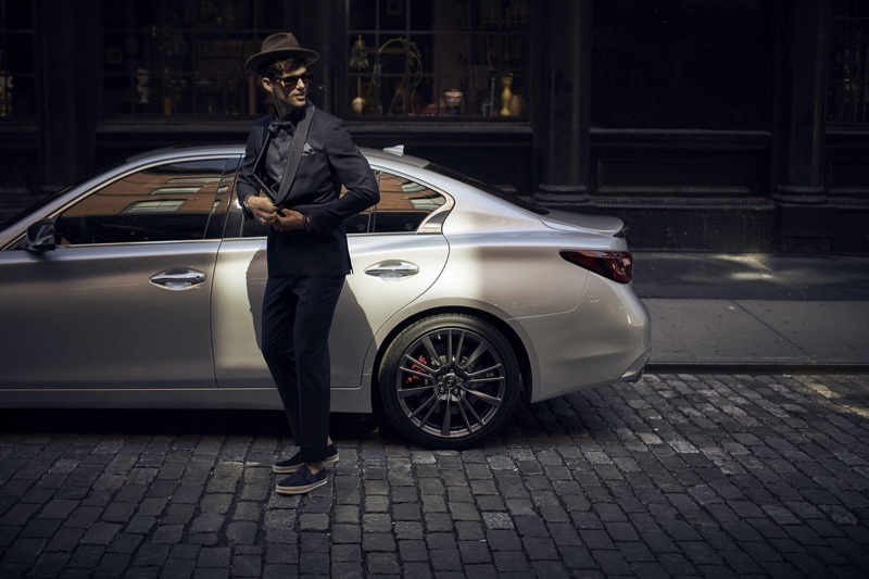 A stylish vision, Max Jablonsky poses in front of an Infiniti car.