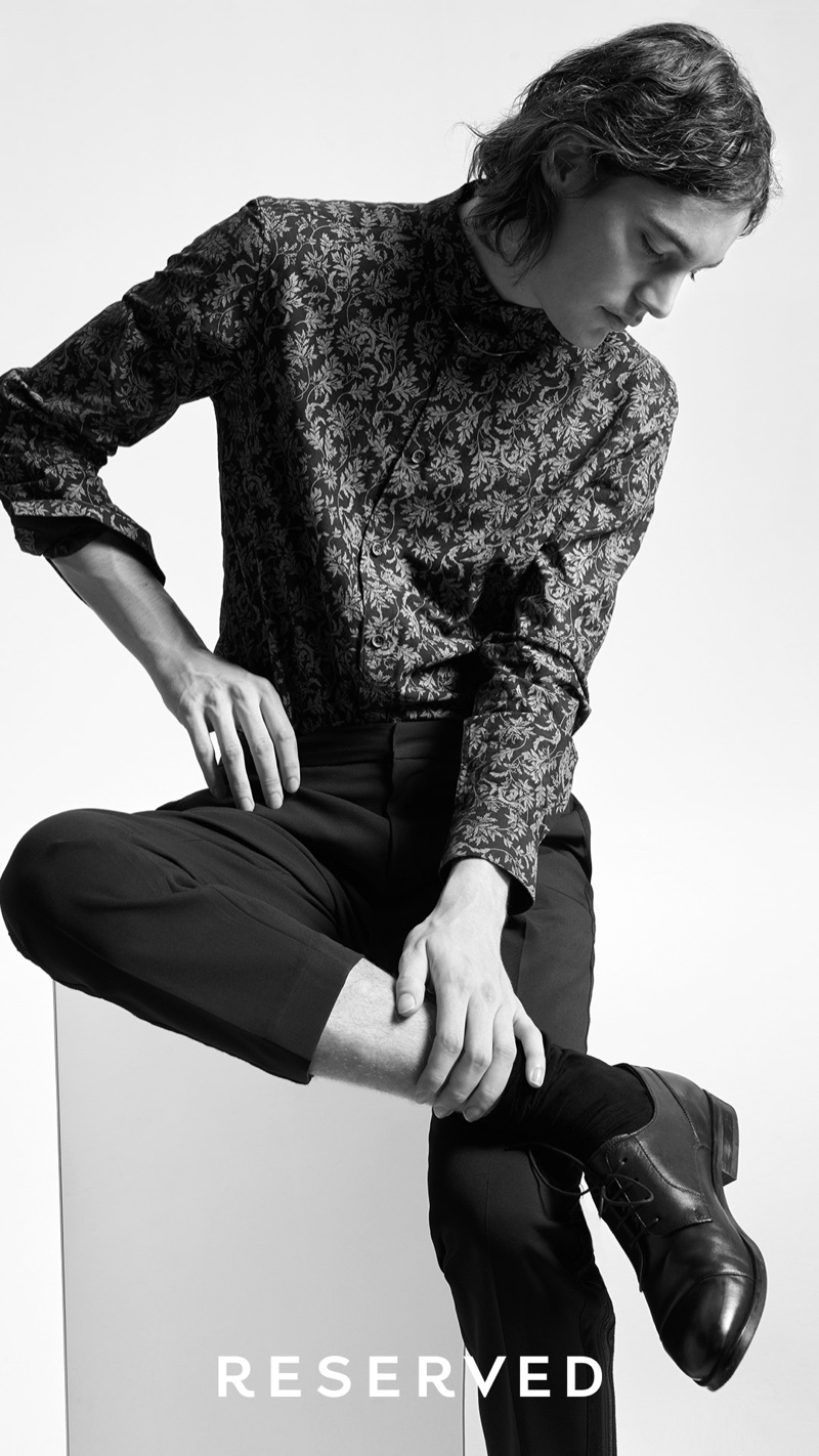 Appearing in a black and white image, Jaco van den Hoven wears a modern look from Reserved.