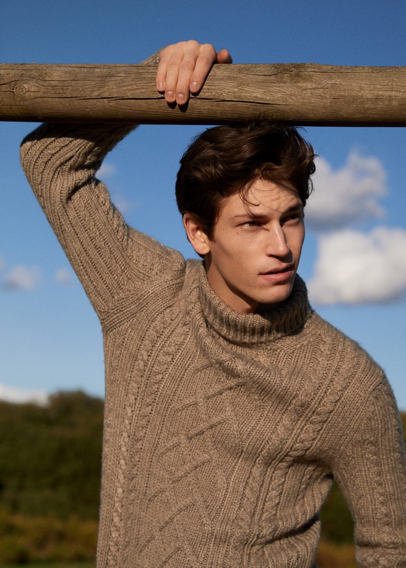 Justin Eric Martin dons a tan cable-knit sweater from Mango.