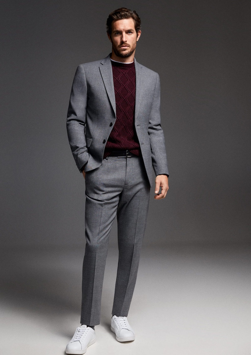 Donning a gray Mango suit, Justice Joslin also wears a knit sweater.