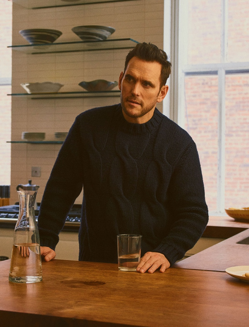 Pictured in the kitchen, Matt Dillon sports a navy cable-knit sweater by Brioni.