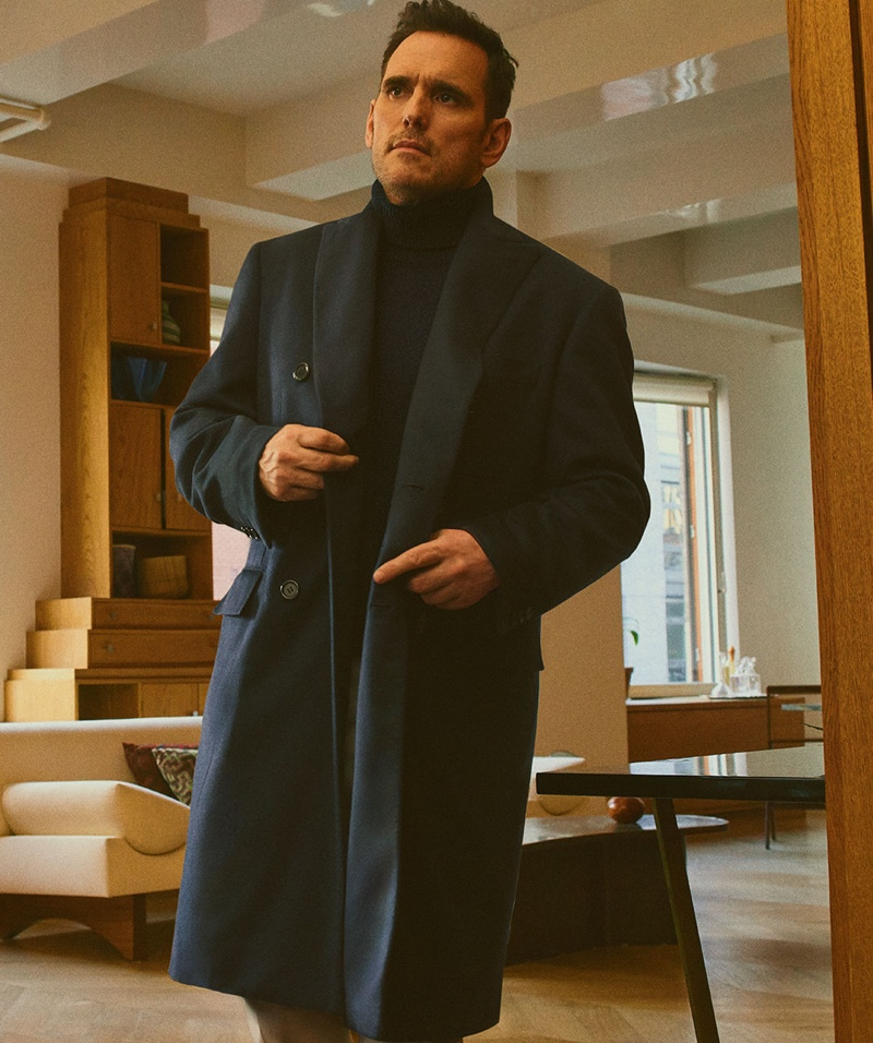Ready to head out, Matt Dillon sports a sleek coat and turtleneck sweater by Brioni.