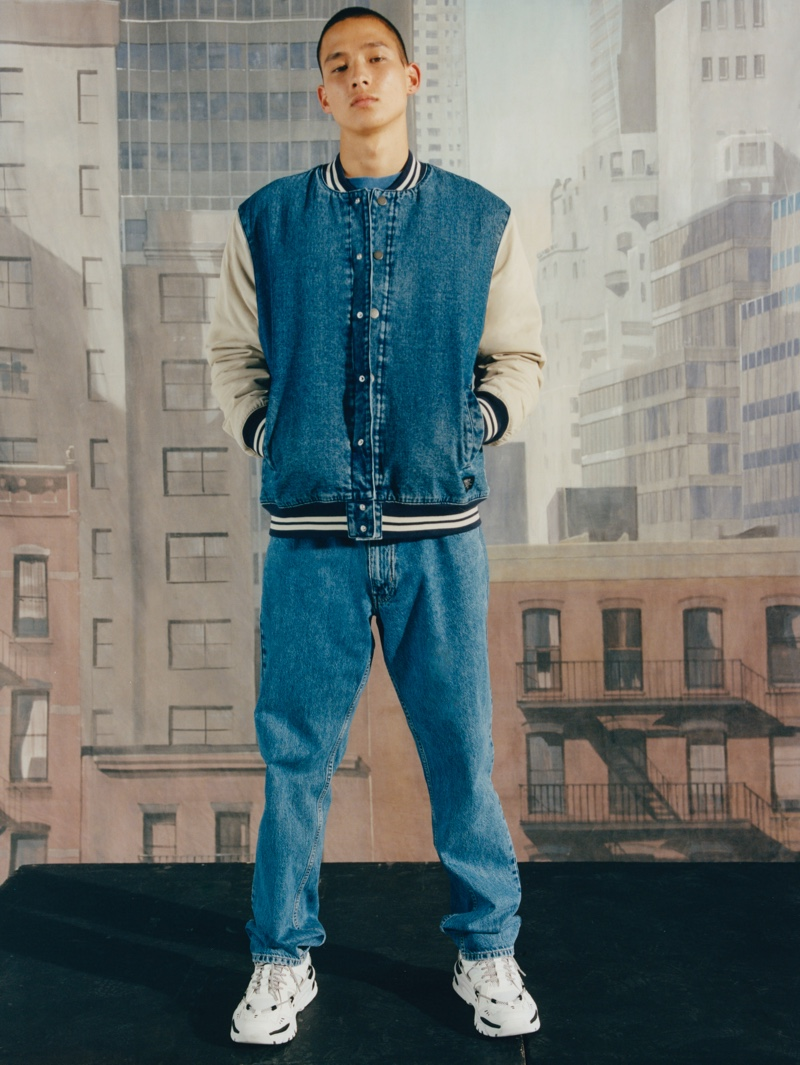 Connecting with Pull & Bear, Tommy Vanden Meerssche wears a denim varsity jacket and relaxed jeans.