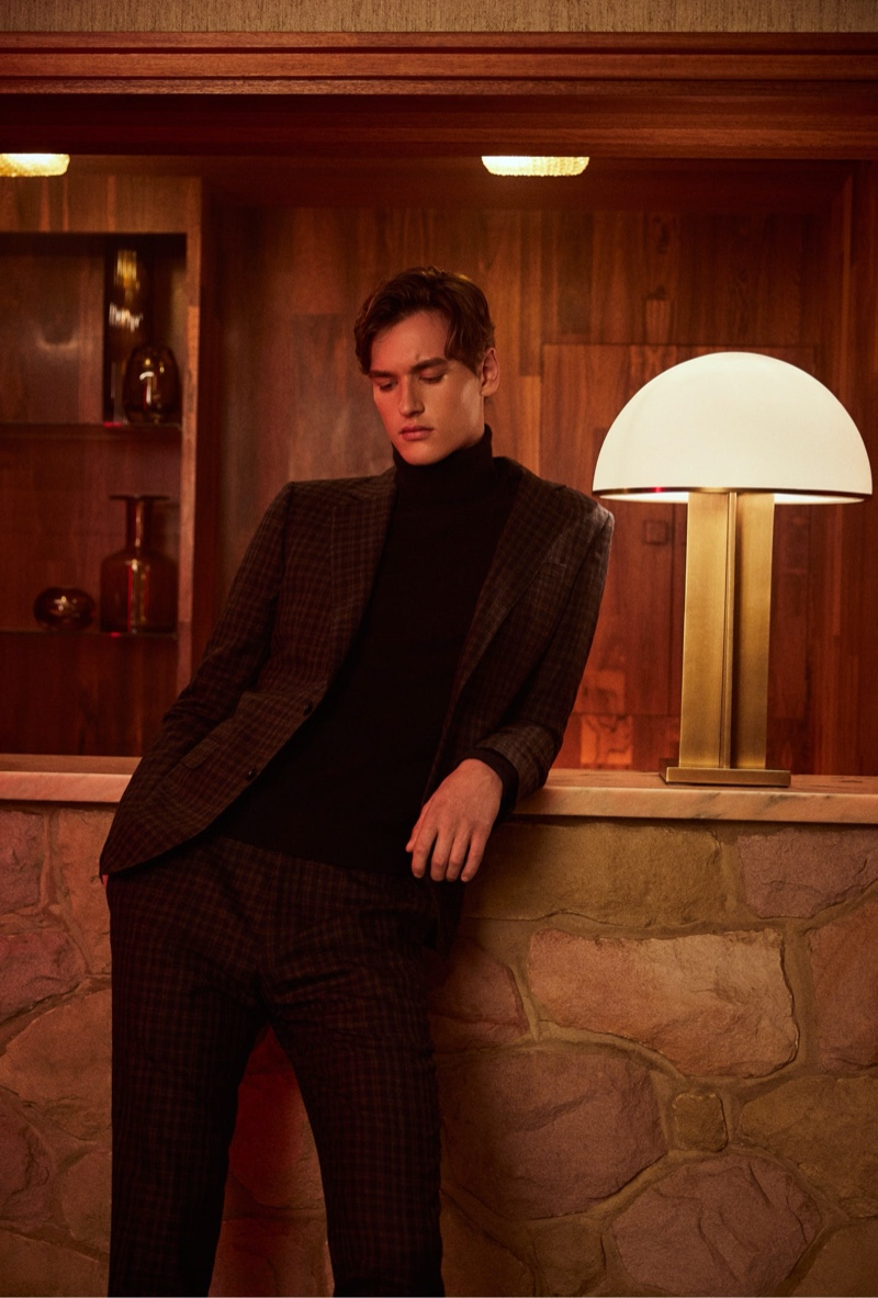 Posing by the bar, Jegor Venned wears Reiss' checked suit with a turtleneck sweater.