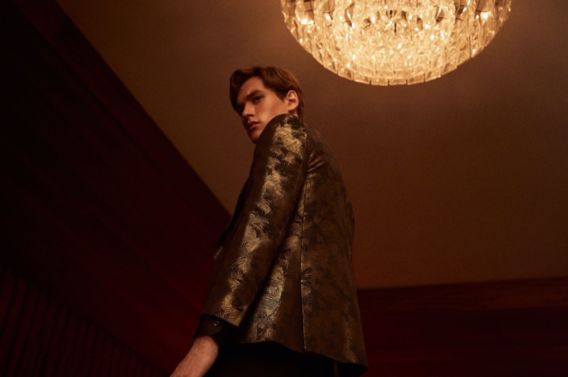 Jegor Venned dons a gold jacquard blazer with black slim-fit jeans from Reiss.