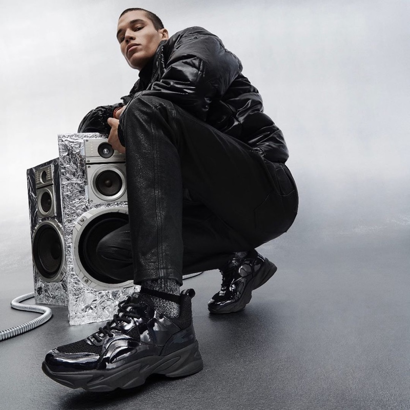 Embracing an all black look, T.J. Moore appears in Steve Madden's holiday 2019 campaign.