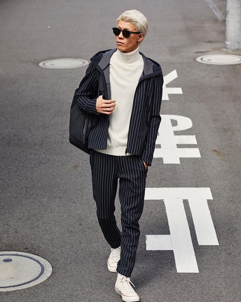 A smart and modern vision, Jumpei models a Todd Snyder + Descente navy pinstripe hoodie jacket $370 and long pants $320.