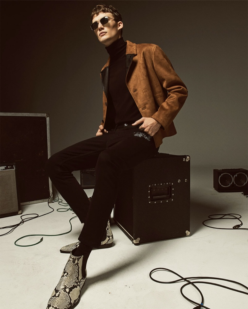 Lukas Adriaensens sports a faux suede jacket with a black turtleneck, pants, and reptile print boots by Zara.