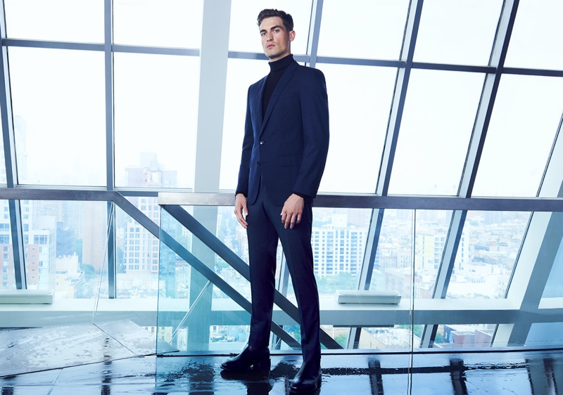 Jason Anthony dons a navy BOSS suit with a black turtleneck for Bloomingdale's.