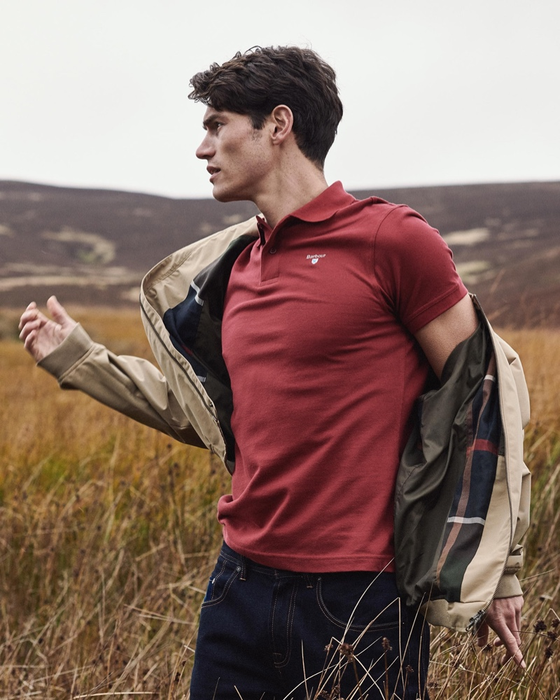 Venturing outdoors, Sam Way models a Barbour polo shirt with one of the brand's signature jackets.