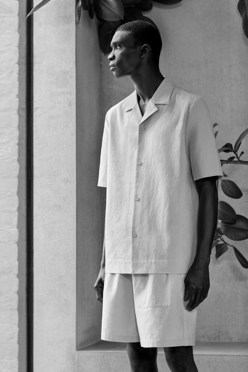 Model Fernando Cabral sports a short sleeved cotton shirt and boxy organic hemp shorts by COS.