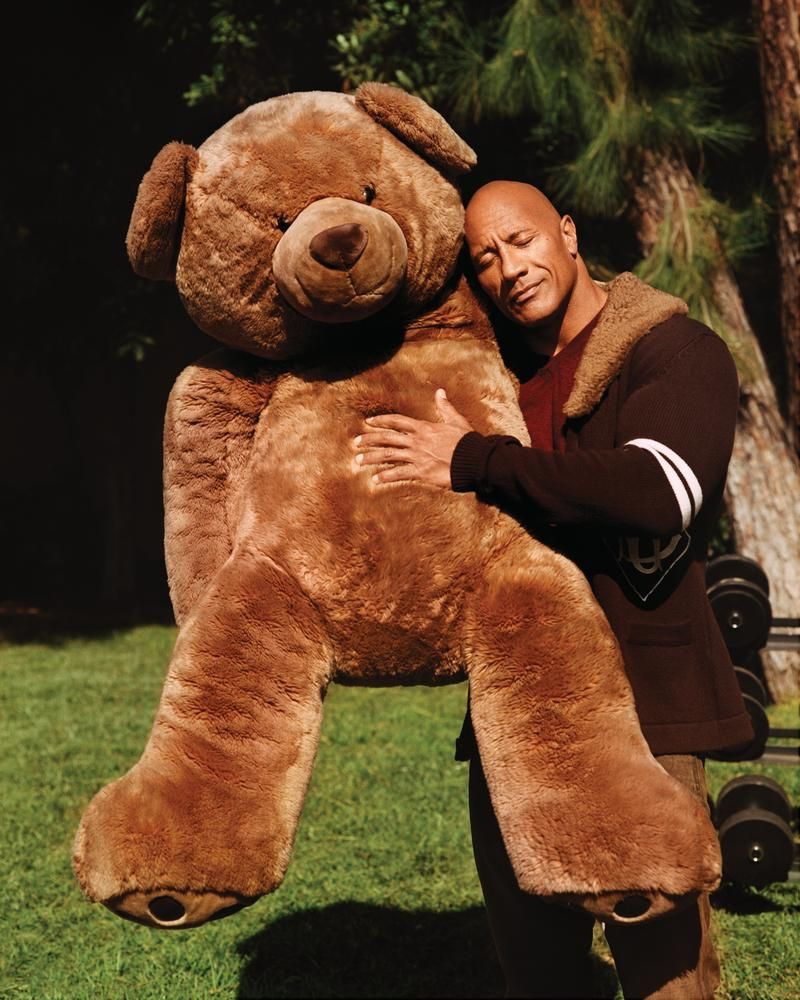 """Hugging a giant teddy bear, Dwayne """"The Rock"""" Johnson sports a Dolce & Gabbana cardigan, Brioni sweater, and Double RL jeans for WSJ. magazine."""