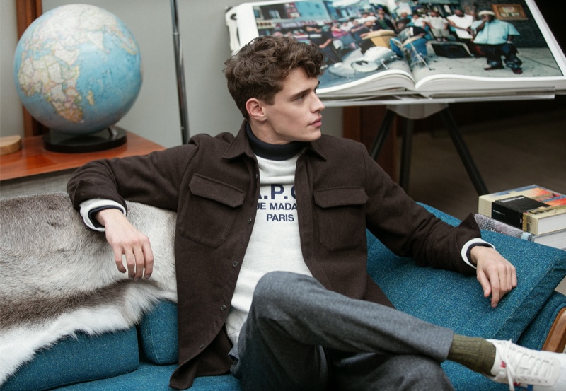 Relaxing, Jordy Baan sports an A.P.C. shirt jacket, Champion sweatshirt, Club Monaco houndstooth trousers, and Onitsuka Tiger California 78 EX sneakers.