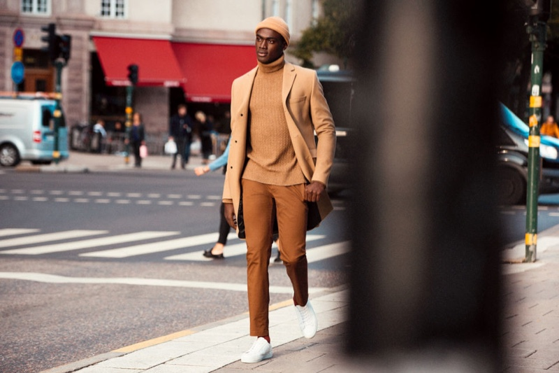 Embracing camel tones, Davidson Obennebo wears a sleek H&M look that includes a classic turtleneck sweater.