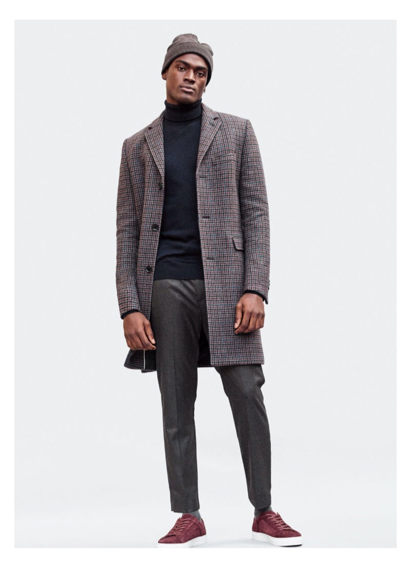 Hitting the studio, Davidson Obennebo models a H&M turtleneck with a checked coat and pleated trousers.