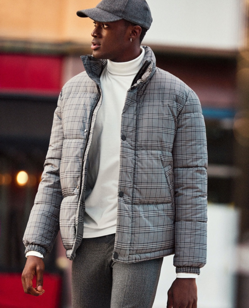 On the move, Davidson Obennebo sports a turtleneck with a checked puffer jacket and trousers from H&M.
