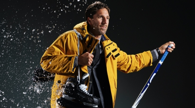 Connecting with Men's Health, Henrik Lundqvist sports a BOSS down jacket, suit jacket, shirt, and tie. Velient Align MX pants, Timberland sneaker boots, and a TAG Heuer watch complete his look.