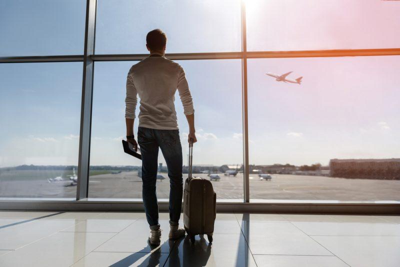 Man at Airport Watching Plane Takeoff