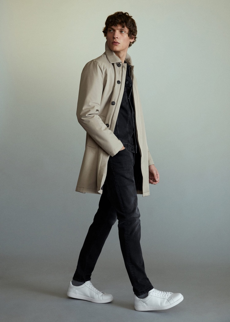 Valentin Caron dons a trench with black fashions from Mango.