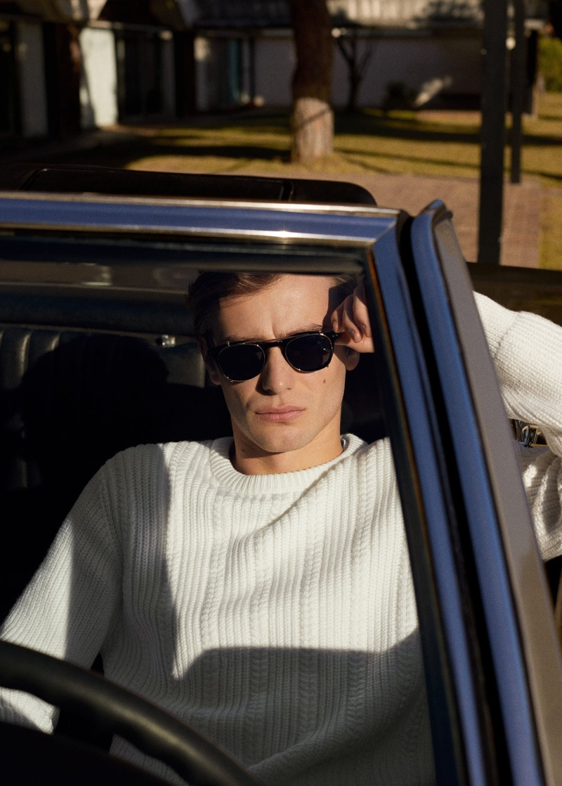 Getting behind the wheel, Ben Allen dons a cable-knit sweater from Mango.