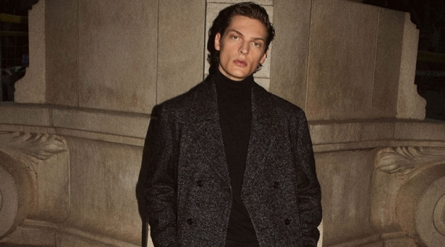 Valentin Caron dons a herringbone coat and turtleneck with boots from Massimo Dutti.