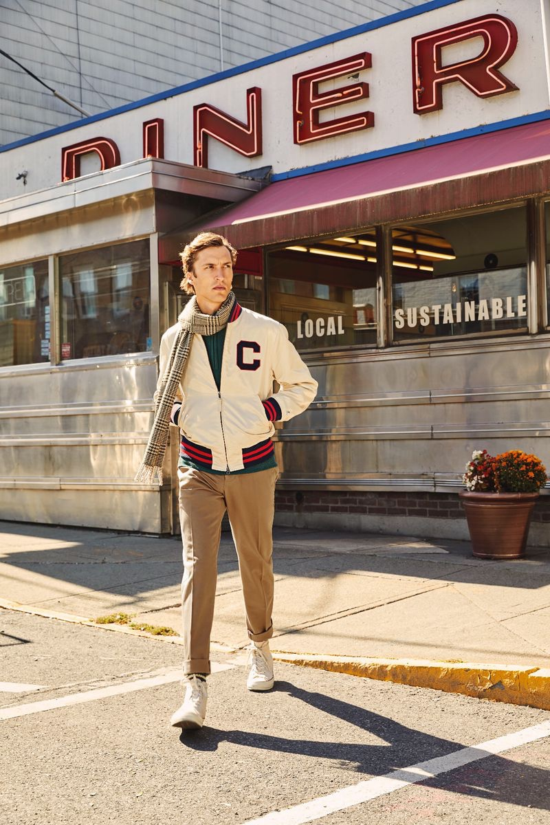 Embracing collegiate style, Tim Dibble dons a Todd Snyder + Champion winged foot Goldenbear bomber jacket $498, Todd Snyder Italian ribbed sweater $268, and a Drake's glen check merino wool scarf $172.