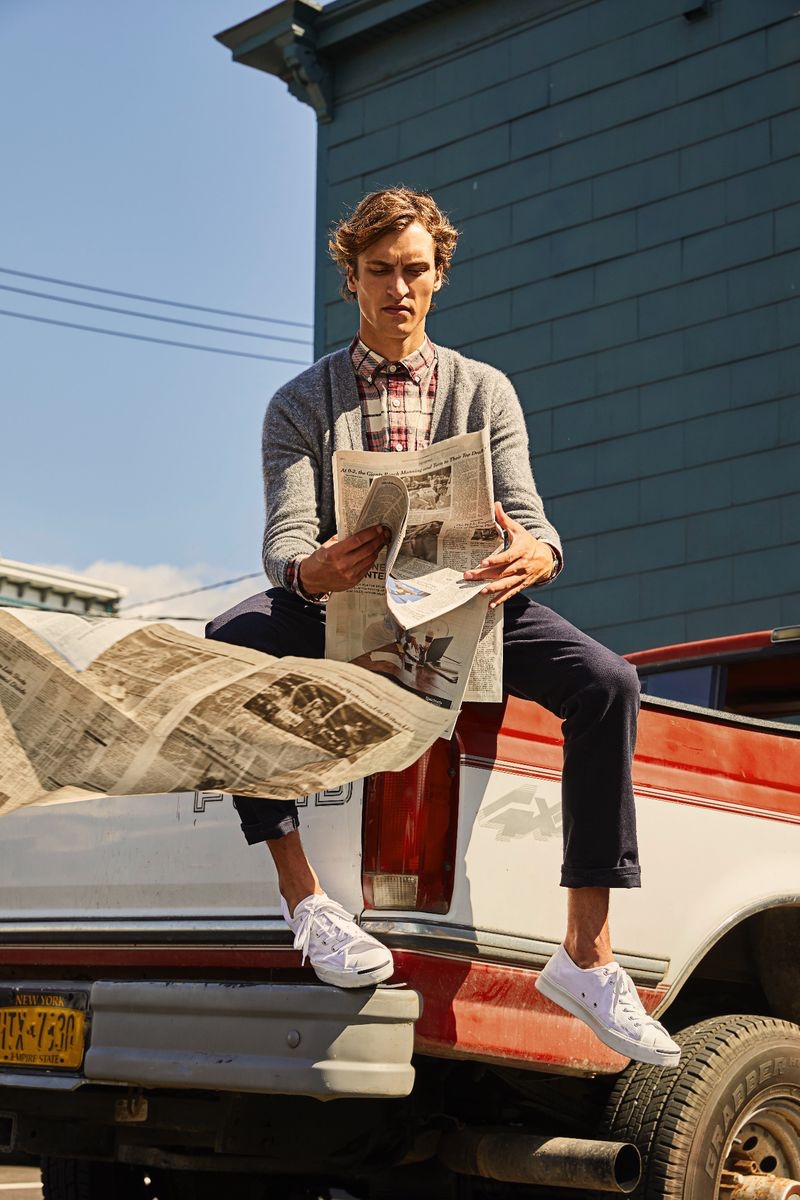 Reading the newspaper, Tim Dibble models a Todd Snyder red plaid flannel shirt $178 and Italian merino cardigan $198.
