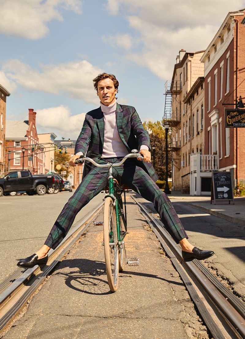 Taking a bike ride, Tim Dibble wears a Todd Snyder Black Label blackwatch checked suit $1,046 and a Todd Snyder cashmere turtleneck sweater $328.