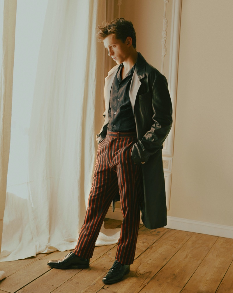Starring in a GQ Style USA photo shoot, Tom Holland wears a shirt and coat by Versace. The young actor also dons striped pants by Ann Demeulemeester with Saint Laurent shoes.
