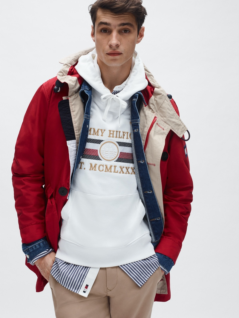 Going sporty, Adrien Sahores models a red parka and logo hoodie from Tommy Hilfiger's spring-summer 2020 collection.