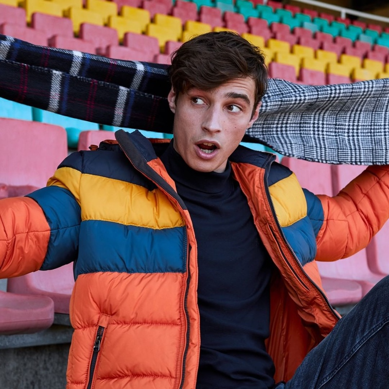 Pouring on the charm, Adrien Sahores sports a colorblock puffer jacket from s.Oliver.