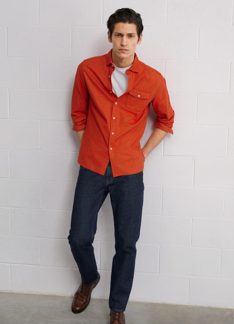 Embracing color, Justin Eric Martin sports a red shirt with dark wash denim jeans by Mango.