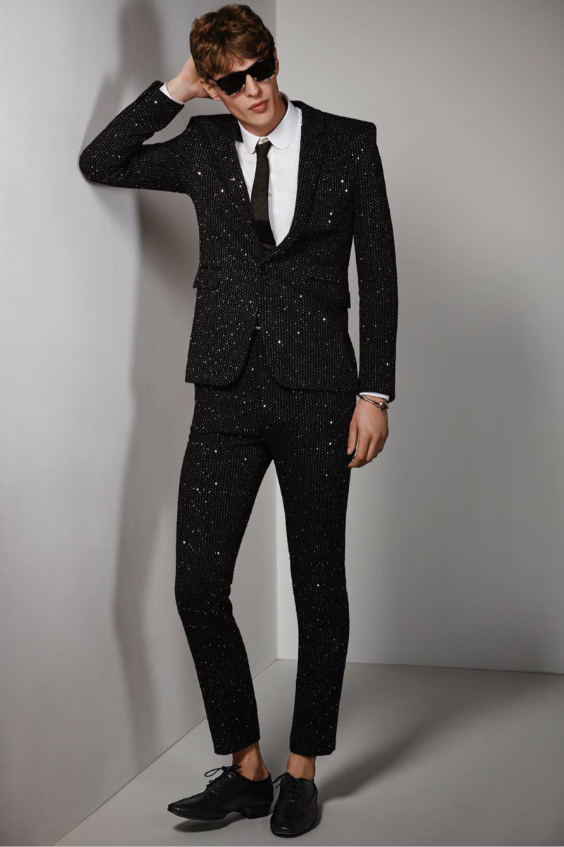 Tim Schuhmacher wears a twill bouclé sequin jacket and pants with a shirt, tie, sunglasses, bracelet, and patent leather oxfords by Saint Laurent.
