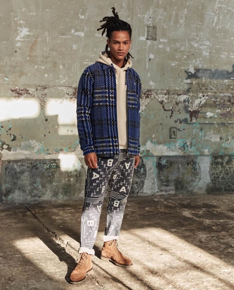 Mixing prints, Olajuwon Anderson wears a Scotch & Soda brushed wool blend jacket and bandana print pants.