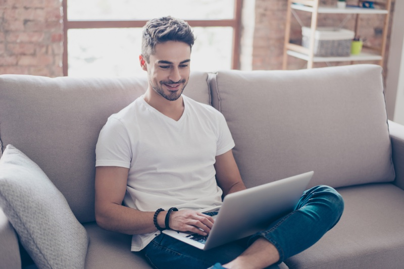 Smiling Man Laptop Couch White Tee Jeans