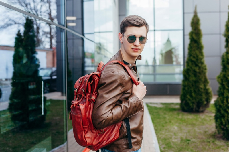 Stylish Man Brown Leather Jacket Red Backpack Sunglasses