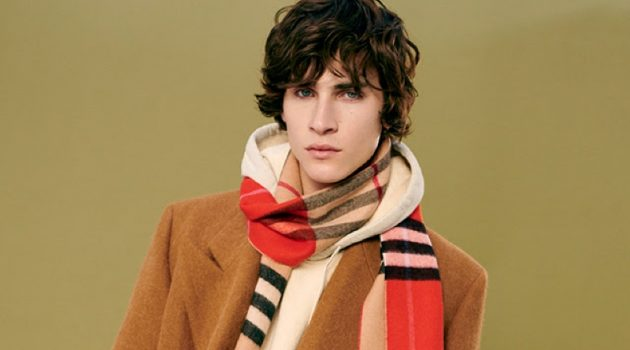 Liam Kelly sports a double-breasted winter coat with a hoodie and Burberry scarf from YOOX.