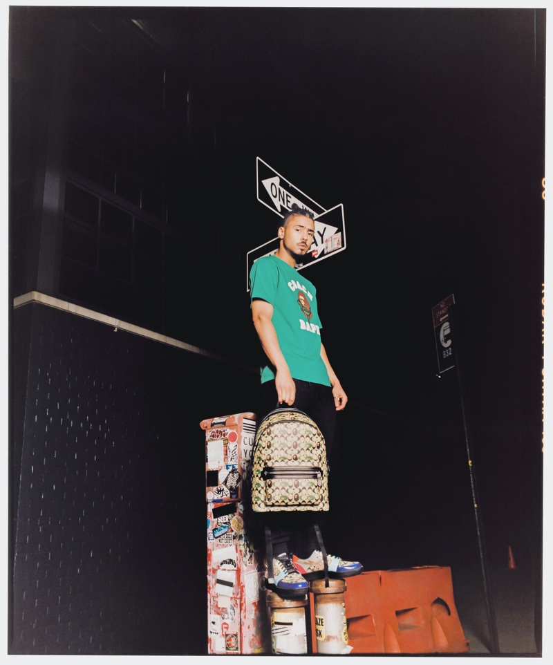 Front and center, Quincy Brown sports a t-shirt, backpack, and sneakers from the Bape x Coach collection.