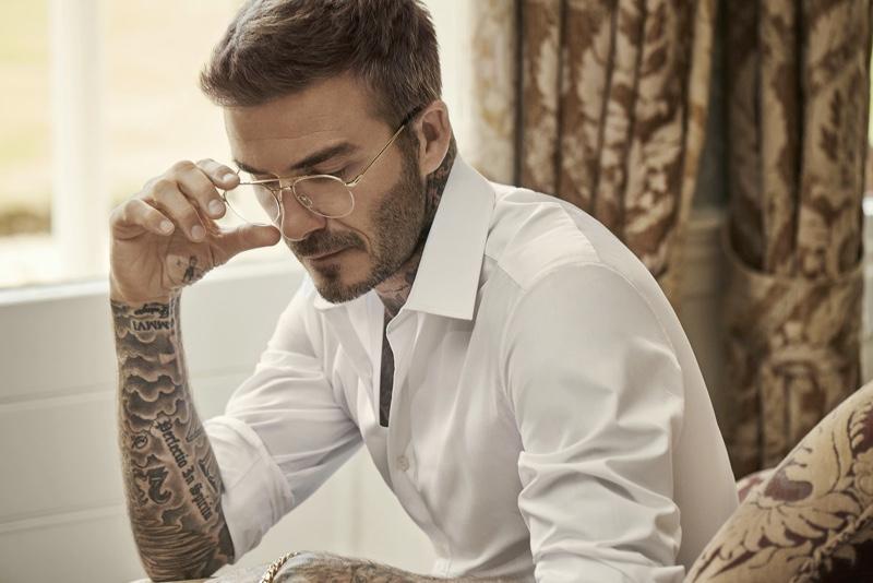 Showcasing a pair of modern glasses, David Beckham dons DB Eyewear.