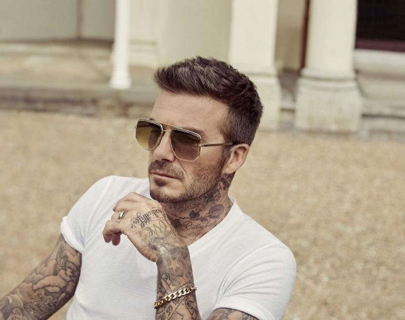 Relaxing in a white t-shirt, David Beckham wears DB Eyewear sunglasses.
