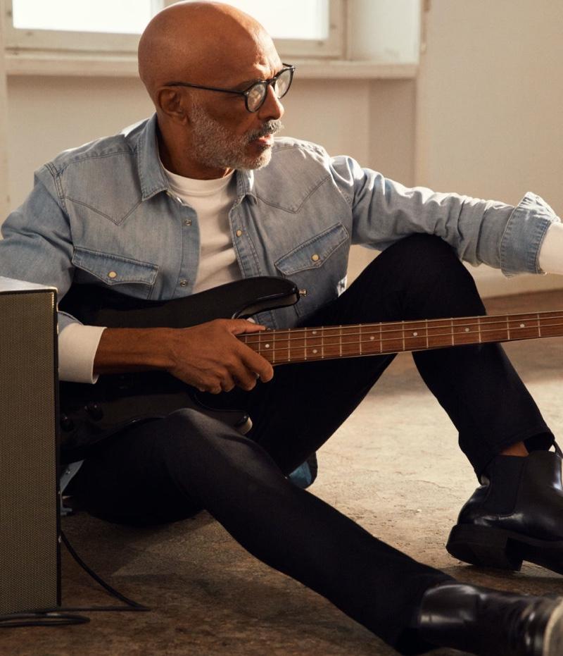 Tuning an electric guitar, Lono Brazil wears H&M's Freefit slim jeans.