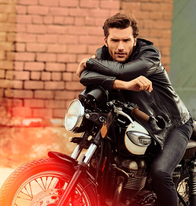 Posing on a motorcycle, Aurelien Muller sports a leather jacket and jeans from IKKS.
