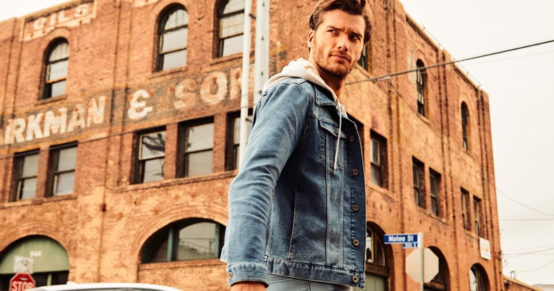 On the move, Aurelien Muller layers in an IKKS jean jacket and hoodie.