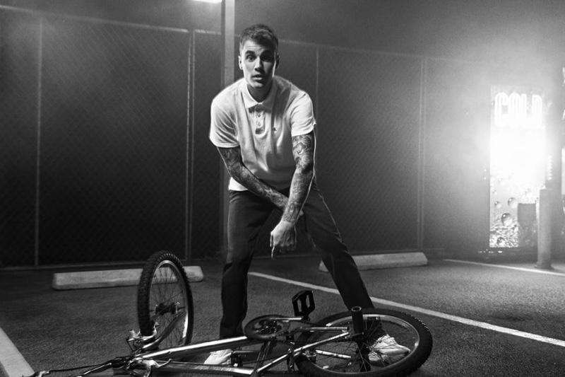 Posing with a bike, Justin Bieber sports a polo shirt and jeans for Calvin Klein's spring-summer 2020 campaign.
